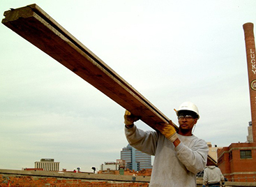 Worker carrying a beam at American Tobacco campus in Durham, NC.