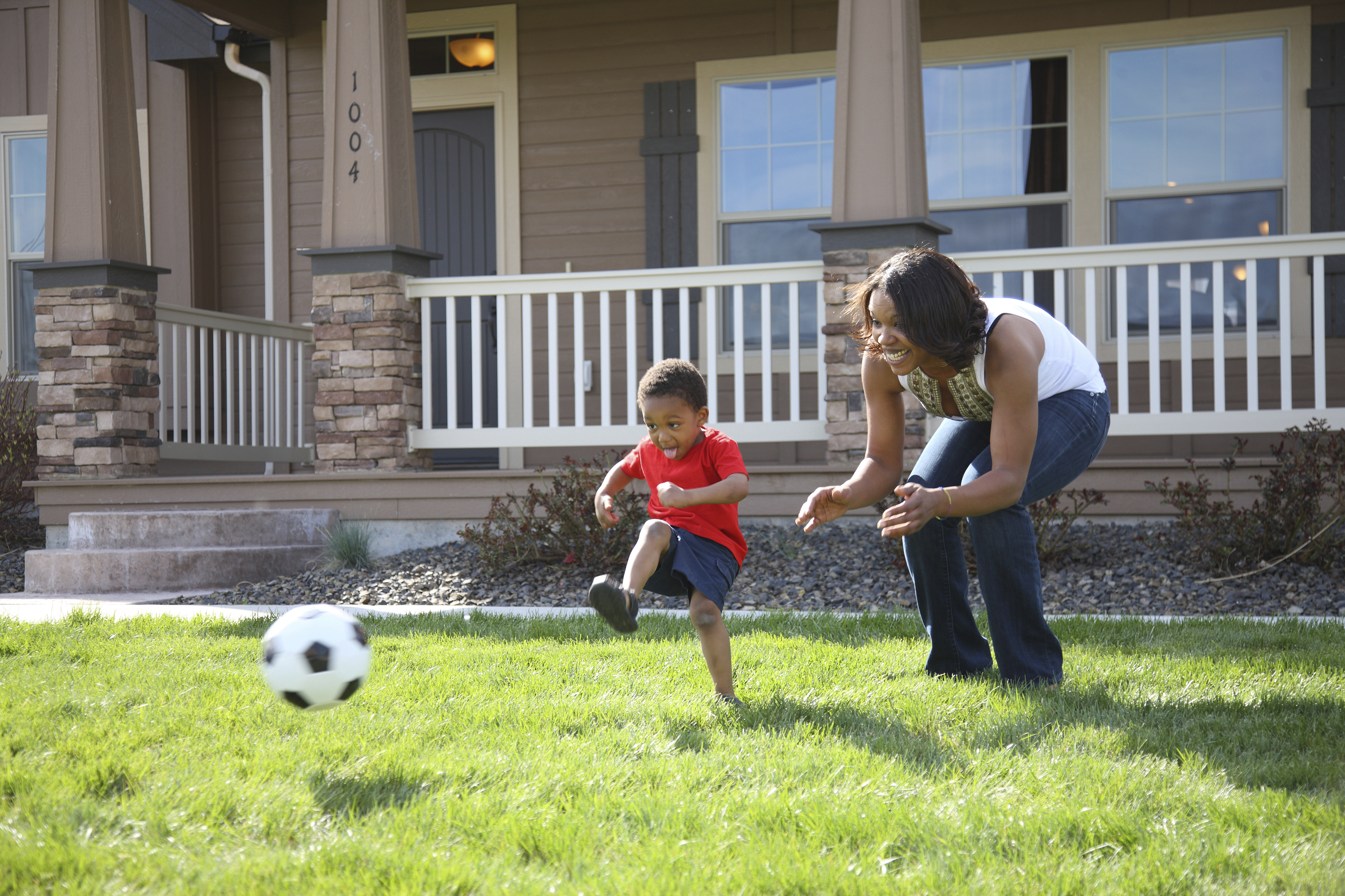 Mom and child playing soccer in yard